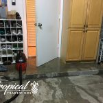 Water pouring out of door into garage